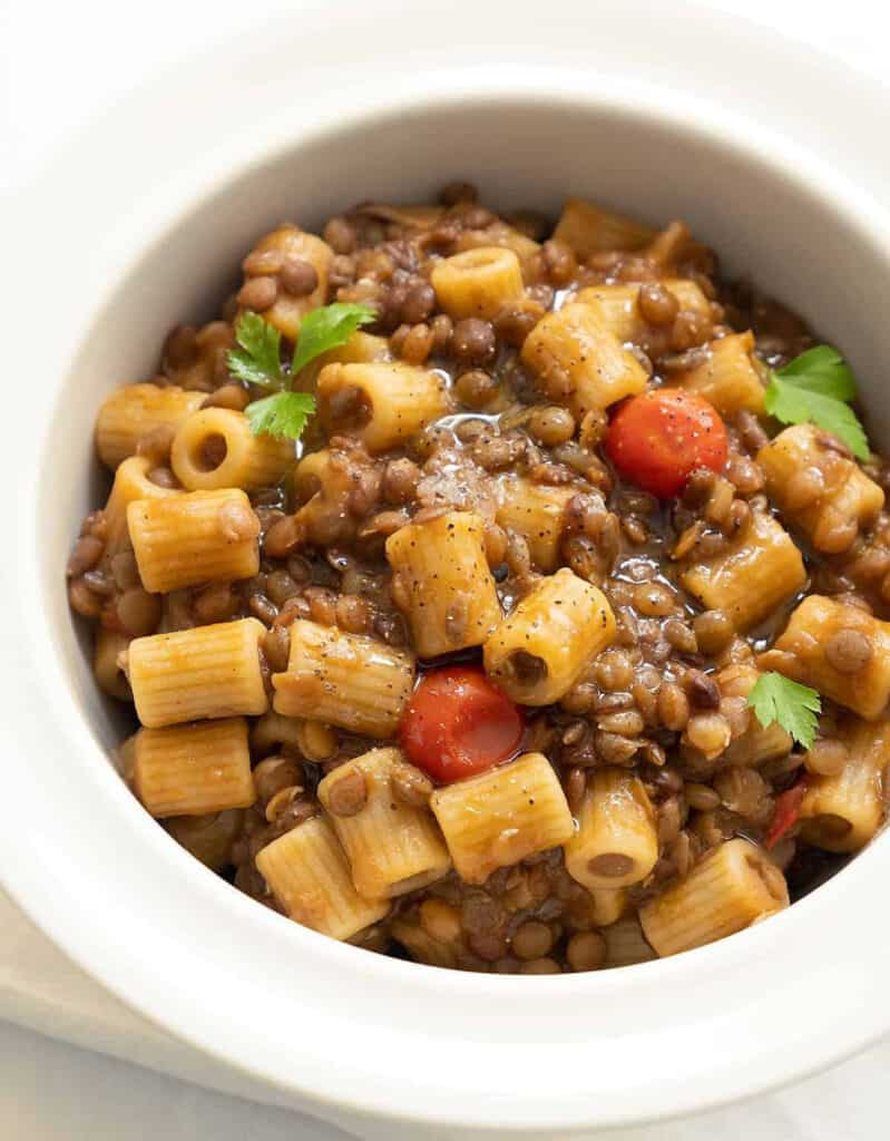 Top view of a white bowl full of pasta with lentils.