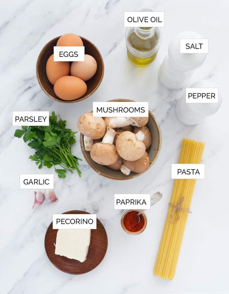 The ingredients for this carbonara with mushrooms are arranged over a white background.