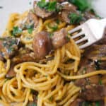 Close-up of a fork lifting some luscious spaghetti carbonara with mushrooms.