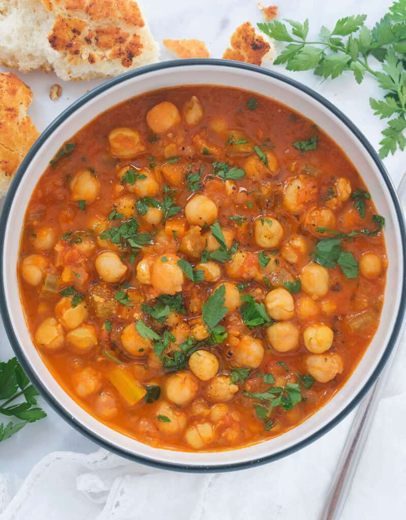 Top view of a white bowl full of chickpea stew served with crusty bread.