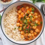Top view of a bowl full of steamed rice and chickpea stew.