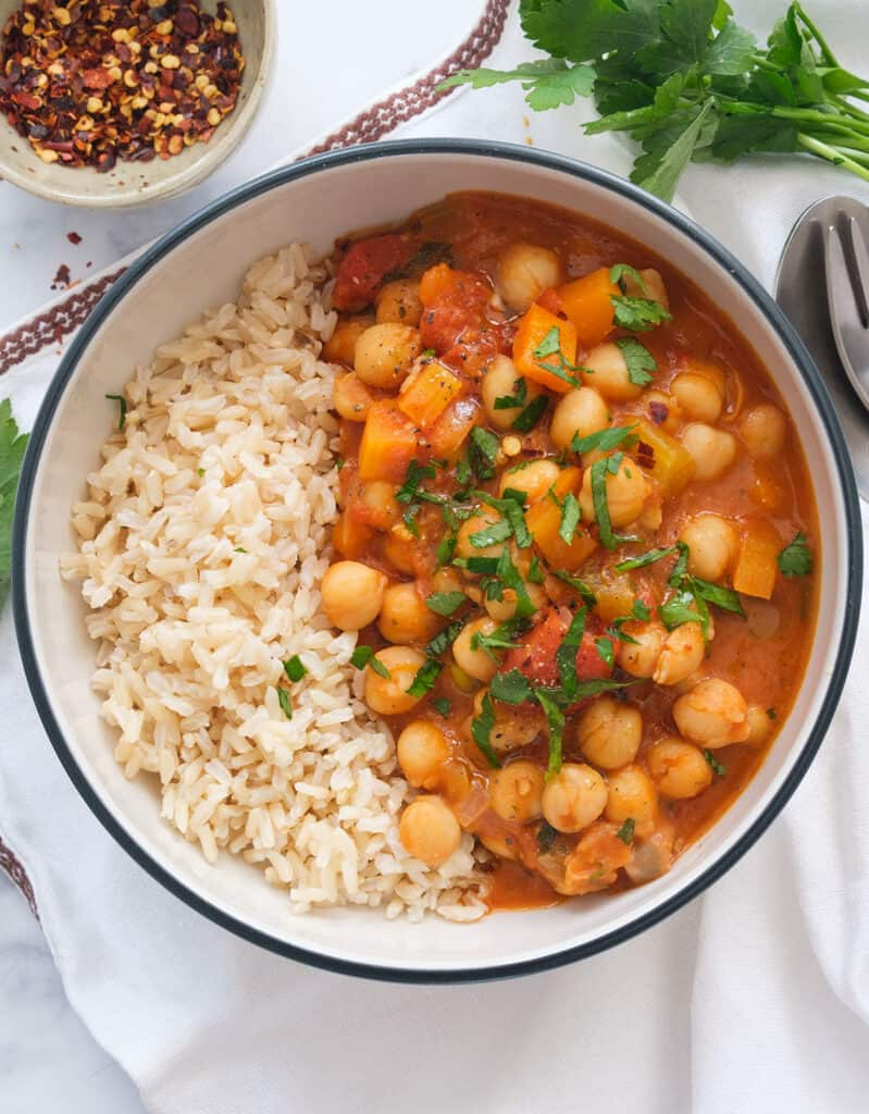 Top view of a bowl full of steamed rice and chickpea stew garnished with chopped parsley.