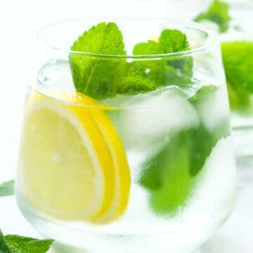 Close-up of a glass full of mint water and slices of lemon.