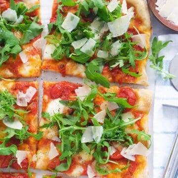 Top view of a rectangular pizza with arugula cut into slices and served with shaved parmesan.