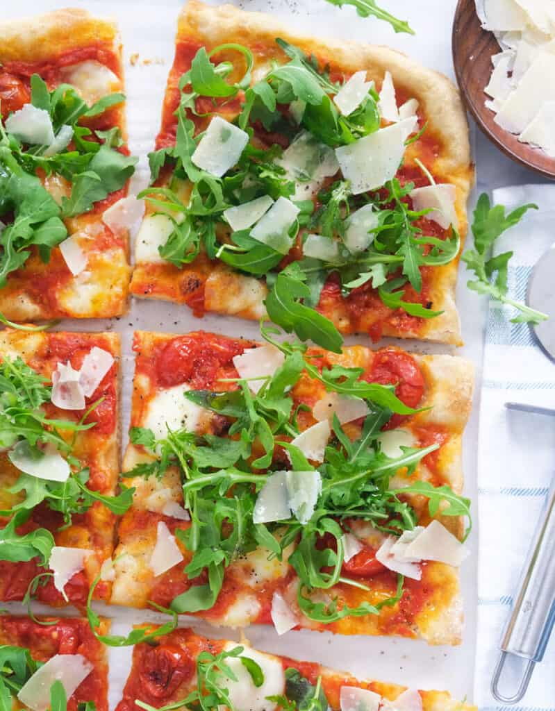 Top view of a pizza with arugula and shaved parmesan cut into slices over a white background.