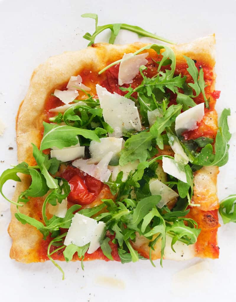 Top view of a single serving of pizza with arugula and shaved parmesan cheese over a white background.