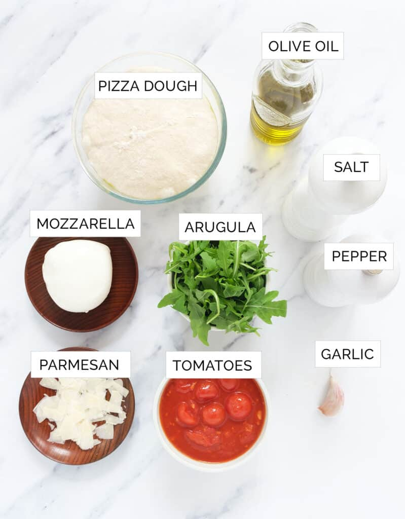 Top view of the ingredients to make this arugula pizza recipes are arranged over a white background.