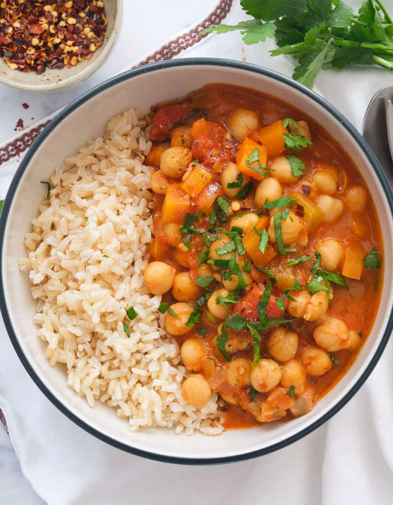 Top view of a white bowl full of rice and chickpea stew made using canned tomatoes.