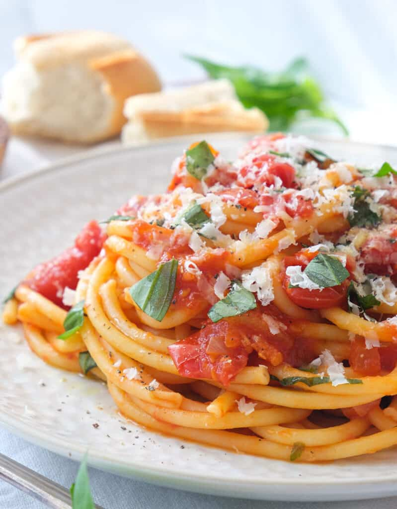 Close-up of a plate full of spaghetti napoletana with tomato sauce and fresh basil.