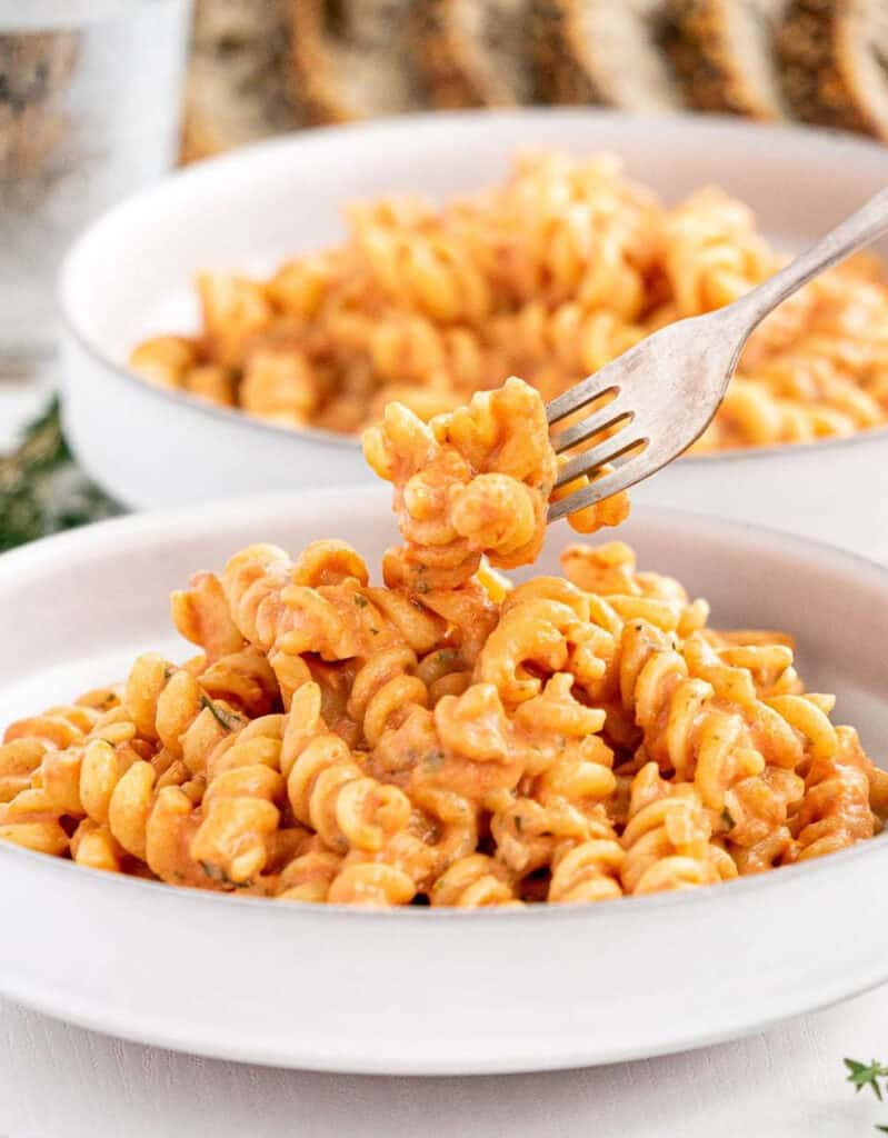 Two white bowls full of fusilli with creamy tomato sauce.