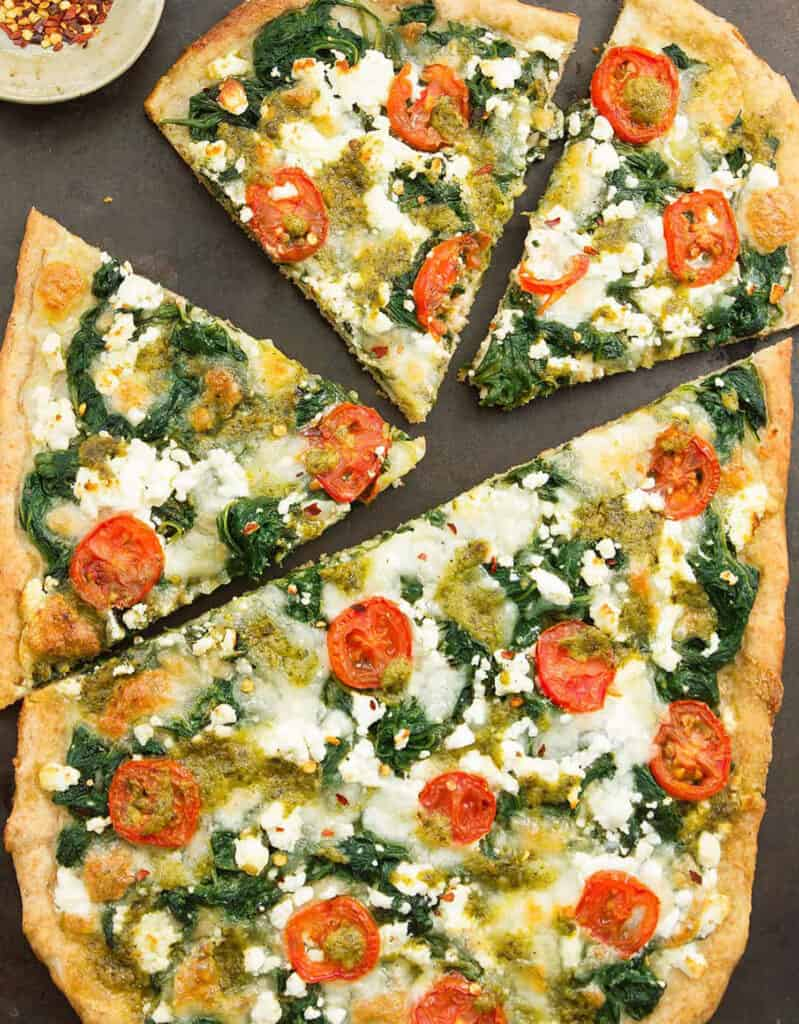 Top view of veggie pizza with spinach and cherry tomatoes over a black background.