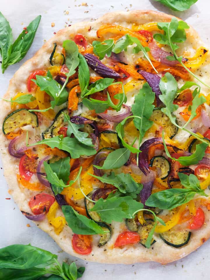 Top view of a veggie pizza with roasted vegetable, arugula and fresh basil.