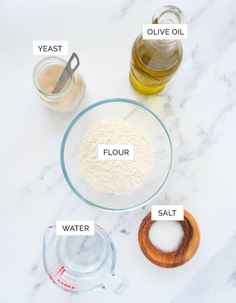 The ingredients to make veggie pizza dough are arranged over a white background.