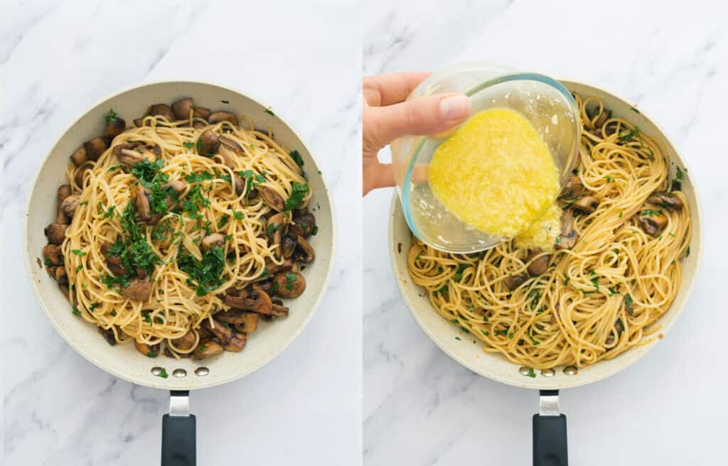 Top view of a skillet full of spaghetti carbonara with mushrooms while a hand is pouring over the egg mixture from a glass bowl.