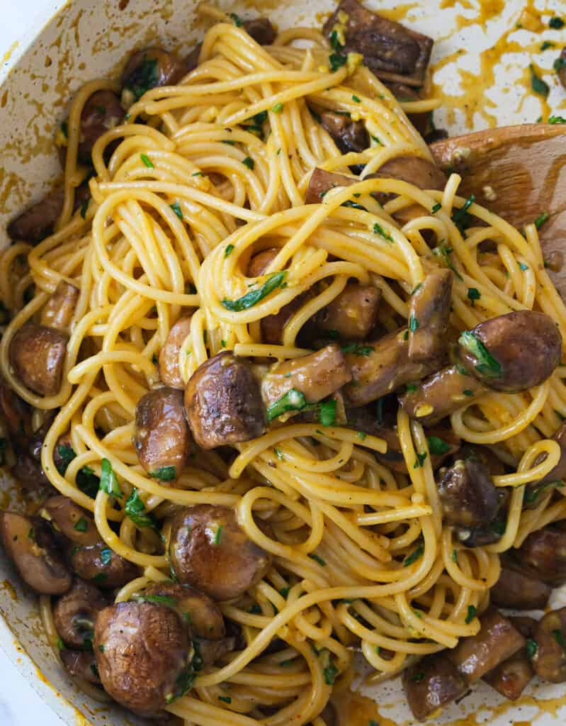 A  wooden spoon is stirring moist and silky spaghetti carbonara with mushrooms in a skillet.