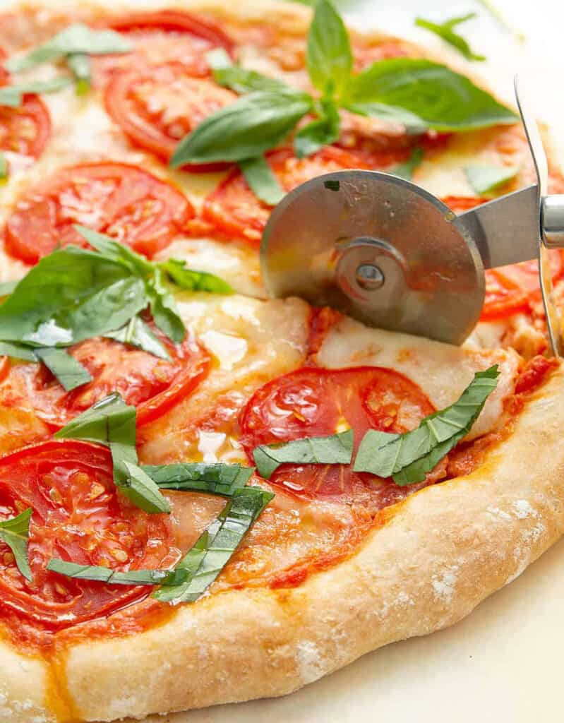 Close-up of a Caprese pizza with fresh tomatoes, one of the most popular veggie pizza recipes in Italy.