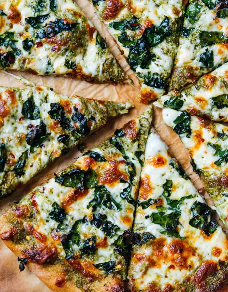 Top view of a vegetarian pizza with kale pesto and melted cheese.