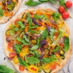 Top view of one of the best veggie pizza recipes topped with roasted vegetables and arugula.